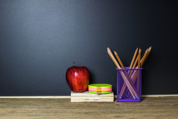 Education concept. Red apple, post it, pencil on wood table with blackboard as background and copy space.