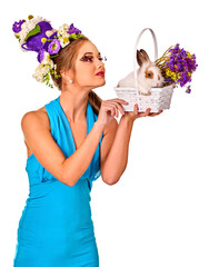 Easter dresses for women. Girl touch bunny . Woman with holiday hairstyle and make up holding rabbit in eggs basket with flowers. Spring discounts on pet products.