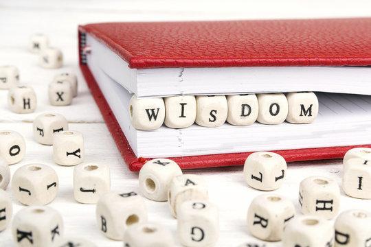 Word Wisdom written in wooden blocks in red notebook on white wooden table.