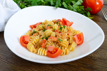 Warm salad with seafood in a white bowl on a wooden background. Pasta Radiatori with crayfish, shrimp, tomatoes, herbs and creamy garlic sauce.