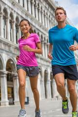Running runner couple man and asian woman tourists jogging in Venice. Summer sport athletes training on travel vacation sightseeing on Piazza San Marco Square, Venice, Italy, Europe.