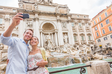 Wall Mural - Rome travel tourists couple at Trevi Fountain in Rome, Italy vacation. Happy young romantic couple traveling in Europe taking self-portrait with smartphone camera. Man and woman happy together