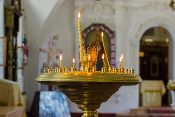 Candles burning in a candlestick in the Orthodox Christian church