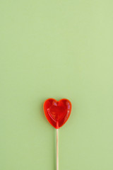 A Lollipop in shape of heart on green background