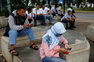 People use smartphones on a sidewalk in Jakarta
