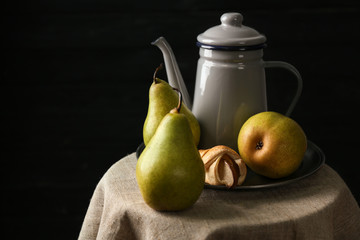 Still life with pears on table against dark background