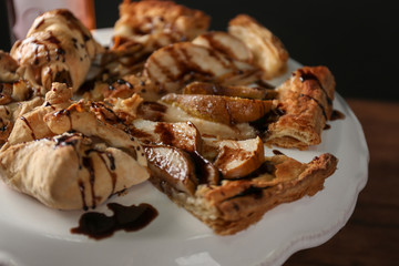 Tasty pear tart with chocolate sauce on cake stand, closeup