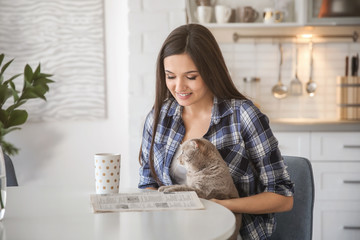 Young woman with cute pet cat sitting at table in kitchen
