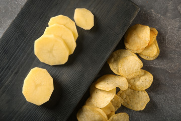 Crispy chips and raw potato on table, top view