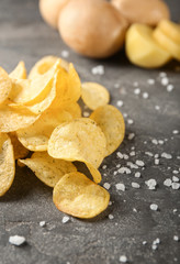 Yummy crispy potato chips with salt on grey table