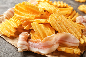 Crispy potato chips with bacon on table, closeup