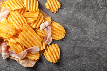 Crispy potato chips with bacon on table, top view