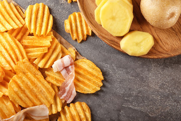 Crispy potato chips with bacon on table