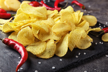 Crispy potato chips with chili pepper on slate plate, closeup