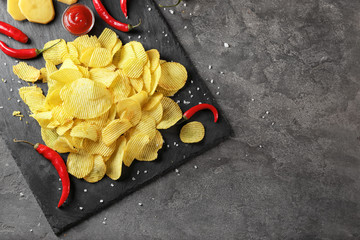 Crispy potato chips with chili pepper and sauce on slate plate, top view