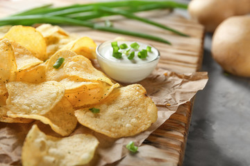 Crispy potato chips with green onion and sour cream on wooden board, closeup