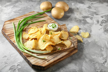 Crispy potato chips with green onion and sour cream on wooden board