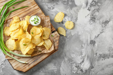 Crispy potato chips with green onion and sour cream on wooden board, top view