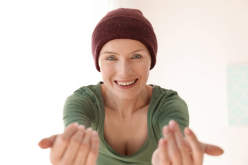 Young woman with cancer in hat on light background