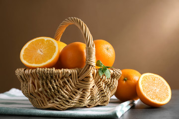 Wicker basket with juicy ripe oranges on table