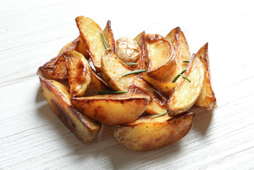 Tasty potato wedges on wooden table