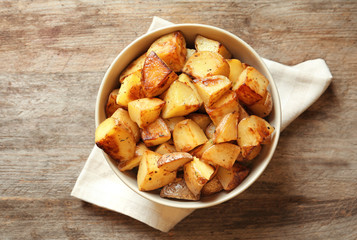 Bowl with tasty potato wedges on table