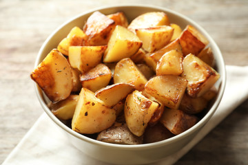 Tasty potato wedges in bowl, closeup