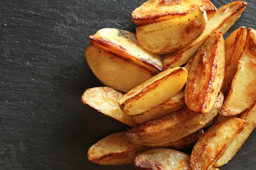 Tasty potato wedges on table