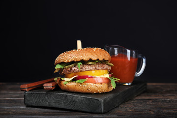 Tasty burger with tomato sauce on wooden board against dark background