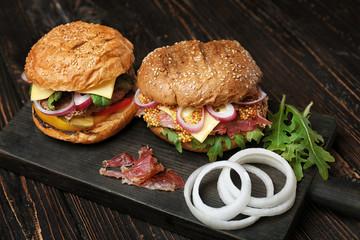 Tasty burgers on wooden board