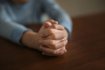 Little boy praying at table, closeup