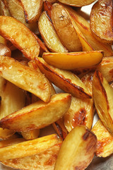 Delicious baked potato wedges, closeup