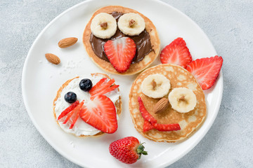 Funny colorful breakfast pancakes with animal faces for kids on white plate. Top view