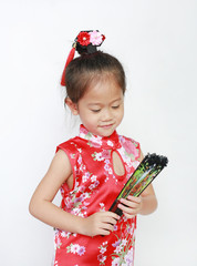 Asian child girl holding Chinese style fan on white background during Chinese new year festival.
