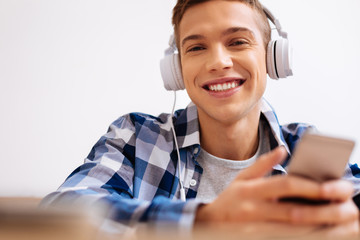 Leisure. Handsome delighted air-haired boy smiling and wearing headphones and listening to music and holding his modern phone