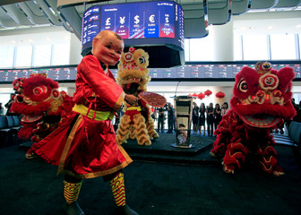 "A dancer wearing a Chinese ""Big Head Buddha"" costume performs along with Dragon dance during the opening bell ringing to mark the first trading day at the brand new Philippine Stock Exchange complex in Bonifacio Global city at Metro Manila"