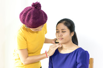 Make-up artist work on her friend.Real people, Girl gets blush on the cheekbones. Powder, rouge