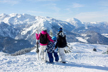 Happy family, mother, father and two children, skiing