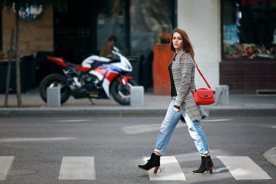 Beautiful young woman crossing street on crosswalk.