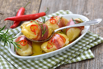 Pikante Käse-Drillinge mit Südtiroler Bauernspeck, Rosmarin und Chilischeiben in Olivenöl gebacken – Hot cheese stuffed rosemary potatoes wrapped in South Tyrolean bacon, baked in olive oil with chili