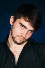 young brunette guy on a dark background