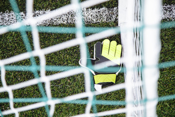 Top view of goalkeeper gloves lying on soccer pitch.