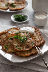 Vegetable pancakes with sour cream on white plate
