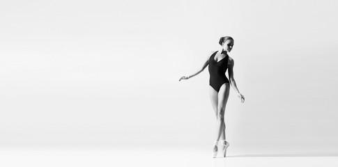 Graceful ballerina dancing in art performance. Young and beautiful ballet dancer in black and white.
