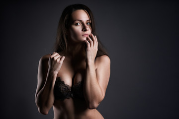 Beautiful sexy woman in lingerie posing on gray studio background, perfect female body