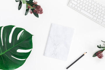Creative workspace. Tropical fllowers and leaves, computer, marble paper blank on white background. Flat lay, top view, copy space