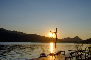 The lamp and ship floating in a river or lake beside the pier with a view of the mountains and sunrise or sunset