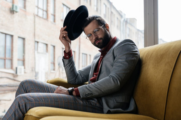 fashionable elegant man in eyeglasses and hat sitting on couch Wall mural