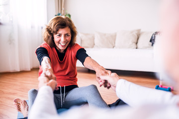 Senior couple doing exercise at home.