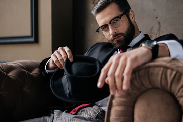 handsome stylish man in eyeglasses holding hat and looking at camera